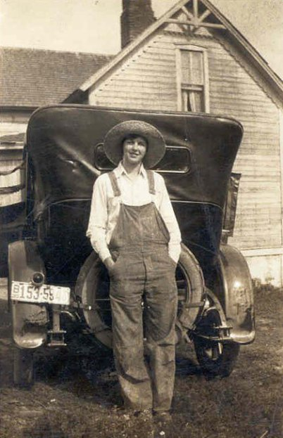A young lady in America is leaning at an old car on a historic brownish photo. Behind the car there is a house visible. She has her hands in her trouser pockets. Plus she has a hat on and smiles to the camera.
