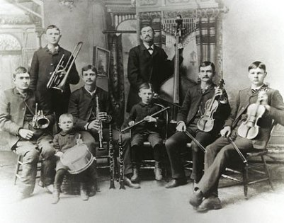 It's a band of seven young people different age, from 25 to 3. In the middle of the background an adult is standing with a bass. All persons have instruments in their hands, 6 are sitting, 2 standing.