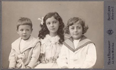On an old photo, black and white, three kids – age around 10 to 12 – are looking to their right. It's two boys and in the middle a girl with curls. The boy on the right has a sailor's costume on. He is my grandpa. Background is grey and shows nothing.
