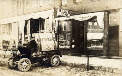 On an historic black and white but brownish photo you see a shop with a sign that tells the owner's name is Bach with a small miniature truck in front of the shop on the road. Two people are sitting.