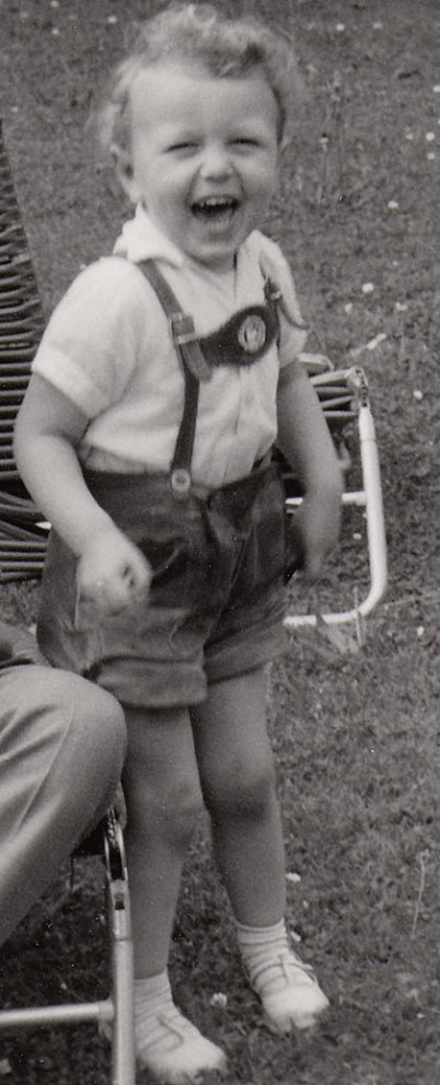 In a very upright photo a little boy in leather trousers – it's the author of that page – is happily laughing to the camera. He has curls on his head and a white shirt on. Plus this boy has white shoes on.