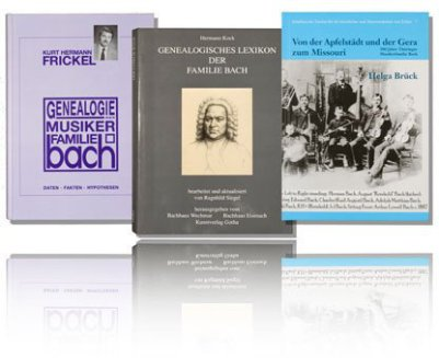 Three Bach genealogy books are hovering in front of white background and a mirror on the bottom. The left book is purple, the book in the middle is black/white and the left is light blue. They are all about the genealogy of the Johann Sebastian Bach Famil