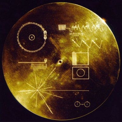 You see the Golden Record = Goldene Schallplatte on a black background. Some engravings which are hard to explain can be located on theat record. There is a shine in the middle.